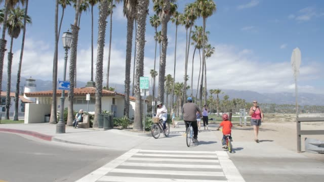 tracking shot of walkers and cyclists on coastal path next to west cabrillo boulevard, santa barbara, california - santa barbara bildbanksvideor och videomaterial från bakom kulisserna