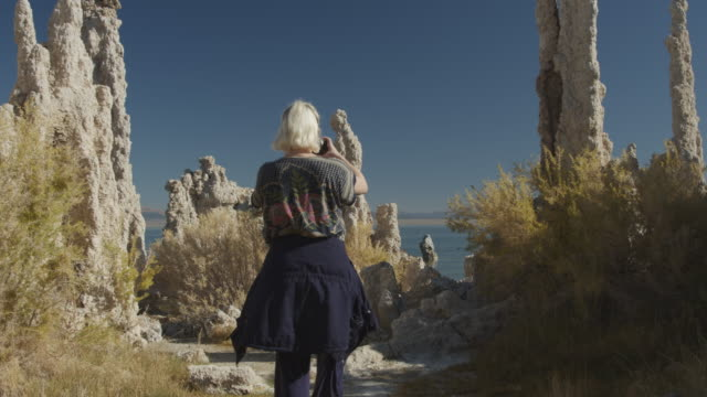 tracking shot of woman photographing tufa rock formations at lake using cell phone / mono lake, california, united states - nur junge frauen stock-videos und b-roll-filmmaterial