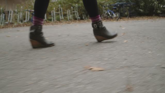 舗装された公園の道を歩くブーツを履いた女性の追跡ショット - ユーラシアエスニシティ点の映像素材/bロール