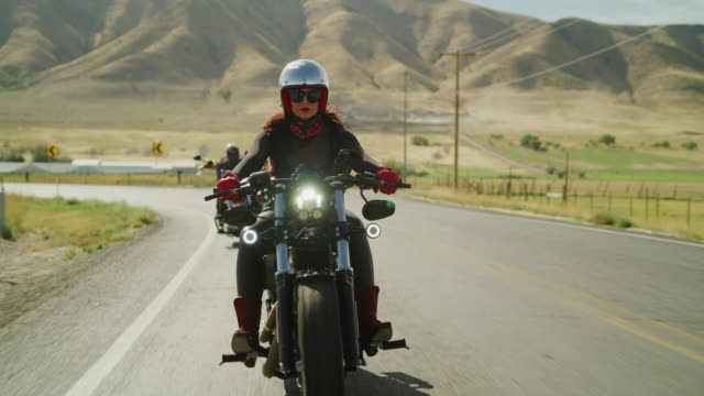 vidéos et rushes de tracking shot of women riding motorcycles waving then passing / payson, utah, united states - payson