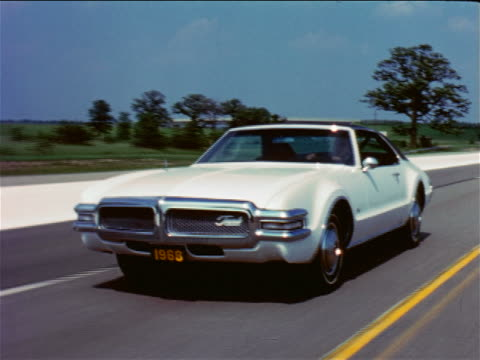 1968 tracking shot oldsmobile toronado driving on country road / industrial - anno 1968 video stock e b–roll