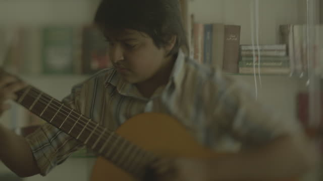 tracking shot on a young arab boy playing a classical guitar. shot raw arri alexa. - plucking an instrument stock videos & royalty-free footage