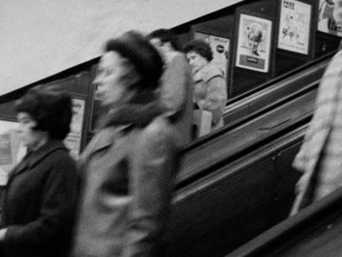 tracking shot on up escalator moving past two busy down escalators at piccadilly circus station 1963 - escalator stock videos & royalty-free footage