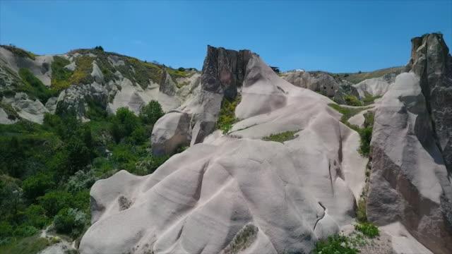 vídeos de stock e filmes b-roll de tracking shot over hills and rocks - exposto ao ar
