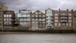 tracking shot passing houses and structures on Thames River bank in London