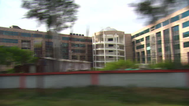 tracking shot passing newly built office buildings in the city of haridwar.  - moving past stock videos & royalty-free footage