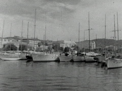 tracking shot past a row of yachts moored in cannes harbour. early 1960s. - cote d'azur stock videos & royalty-free footage