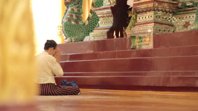 Tracking shot past a woman praying inside the Shwedagon Pagoda.