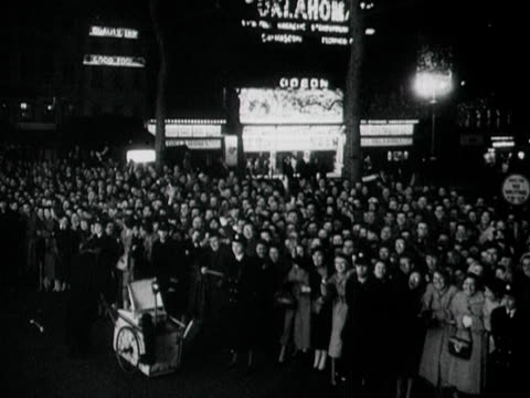 tracking shot past huge crowds waving to the camera at the british premiere of oklahoma at the odeon leicester square 1956 - odeon kinos stock-videos und b-roll-filmmaterial