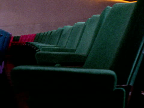 tracking shot past rows of empty seats in the odeon cinema on leicester square 1969 - odeon kinos stock-videos und b-roll-filmmaterial