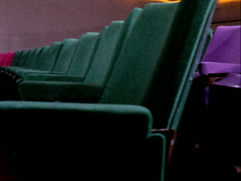 tracking shot past rows of empty seats in the odeon cinema on leicester square. 1969. - odeon cinemas点の映像素材/bロール