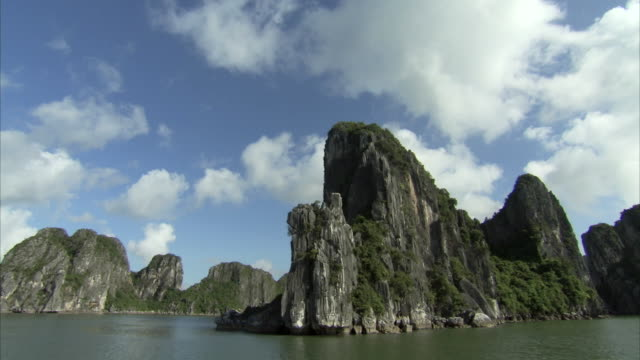 tracking shot past some of the forested islands of halong bay, vietnam. - pacific islands stock videos and b-roll footage