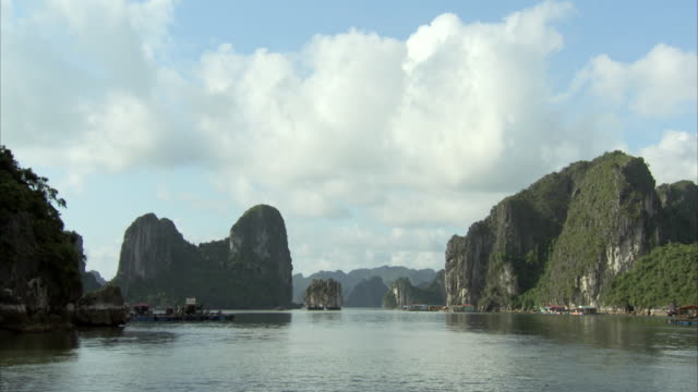 tracking shot past some of the forested islands of halong bay, vietnam. - halong bay stock videos and b-roll footage