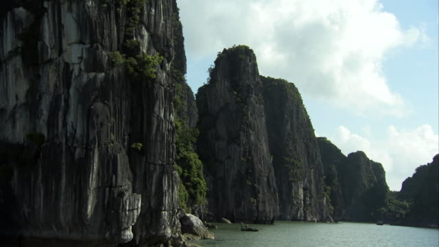 tracking shot past some of the islets of ha long bay, vietnam. - 石灰岩点の映像素材/bロール