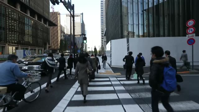 Tracking shot pedestrians walk across a road in the Otemachi central business district of Tokyo Japan on Thursday Nov 14 2013 Otemachi central...
