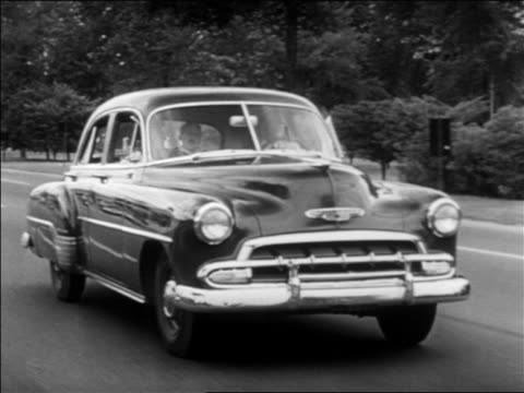 B/W 1952 tracking shot people driving Chevrolet (may be a Fleetline) on tree-lined suburban street / industrial