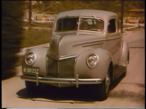 1939 tracking shot people driving ford on suburban street - 1939 stock videos and b-roll footage