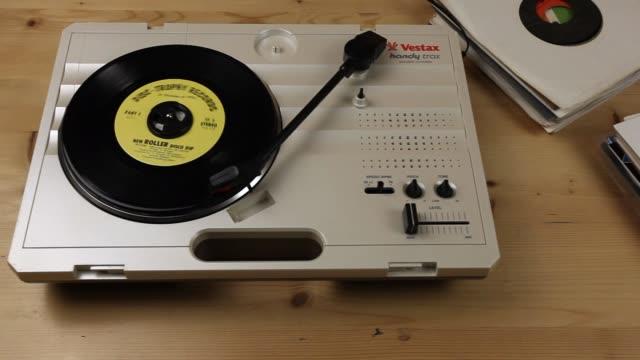 tracking shot playing portable record deck - schallplatte stock-videos und b-roll-filmmaterial