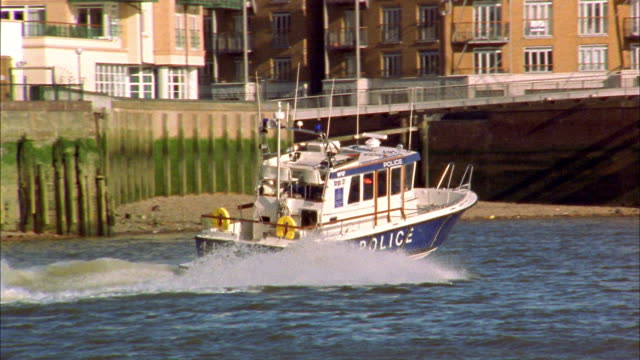 tracking shot police patrol boat on thames river / london - police boat stock videos and b-roll footage
