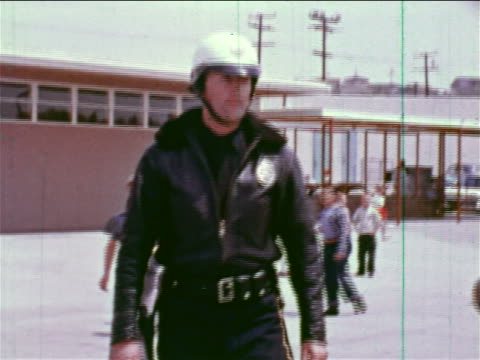 1964 tracking shot policeman in uniform + helmet walking on busy playground / educational