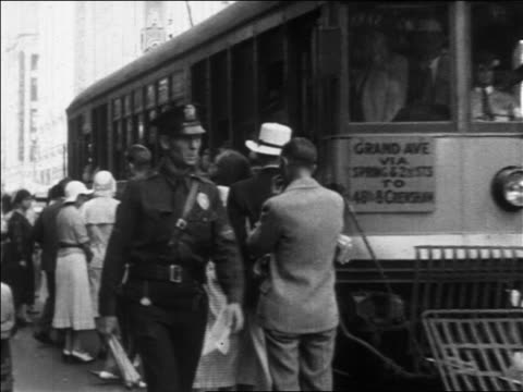 vídeos y material grabado en eventos de stock de b/w 1930 tracking shot policeman walking on busy sidewalk / trolley moving on street / los angeles, ca - 1930