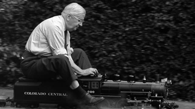 b/w 1951 tracking shot profile senior man riding mini steam train - whatif点の映像素材/bロール
