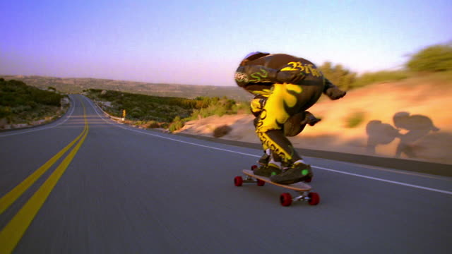 MS tracking shot REAR VIEW two skateboarders with helmets speeding on mountain road