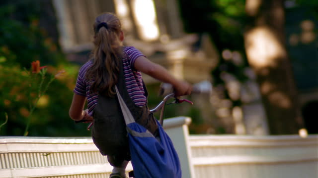 CANTED tracking shot REAR VIEW young girl riding bicycle on sidewalk + delivering newspaper