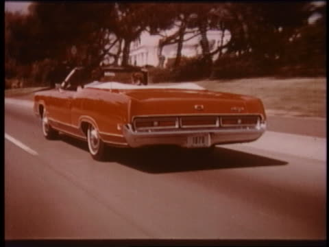 1970 rear view tracking shot red convertible mercury marquis driving on suburban street - ford motor company stock videos and b-roll footage