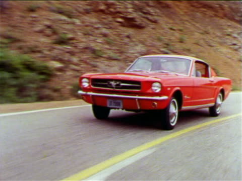 1965 tracking shot red Ford Mustang driving on mountain road toward camera / industrial