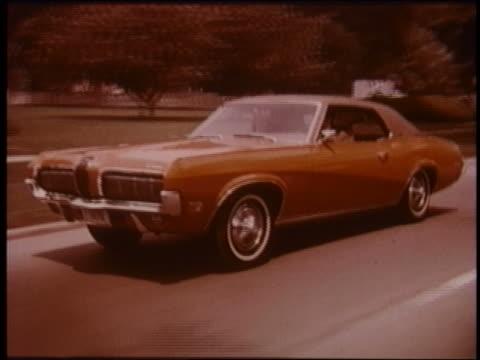 vídeos de stock e filmes b-roll de 1970 tracking shot red mercury cougar driving on suburban street - 1970