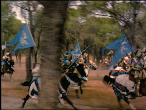 tracking shot REENACTMENT crowd of 6th century knights carrying swords + flags running on horseback past trees