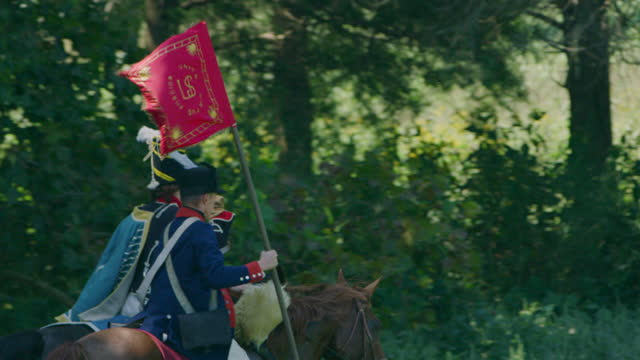 tracking shot of two horsemen galloping side by side with a pulaski legion flag - bridle stock videos & royalty-free footage
