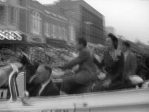 b/w 1960 tracking shot richard pat nixon riding in convertible on crowded town street / michigan - richard nixon stock-videos und b-roll-filmmaterial
