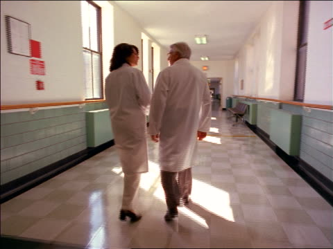 REAR VIEW tracking shot senior male + female doctors walking down hospital corridor talking