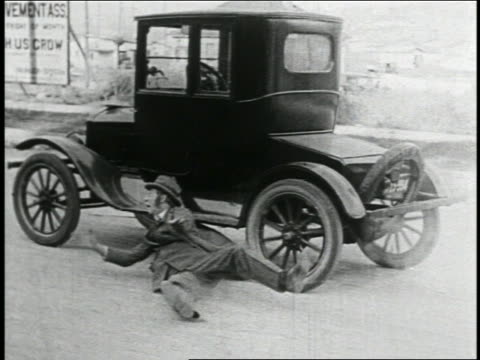 b/w 1925 tracking shot shouting man being dragged by runaway car on street / feature - 1925 stock videos & royalty-free footage
