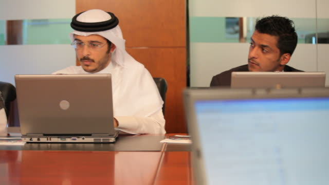 tracking shot showing arab businessmen and women sitting around a conference table working on their laptops. - businesswoman stock videos & royalty-free footage