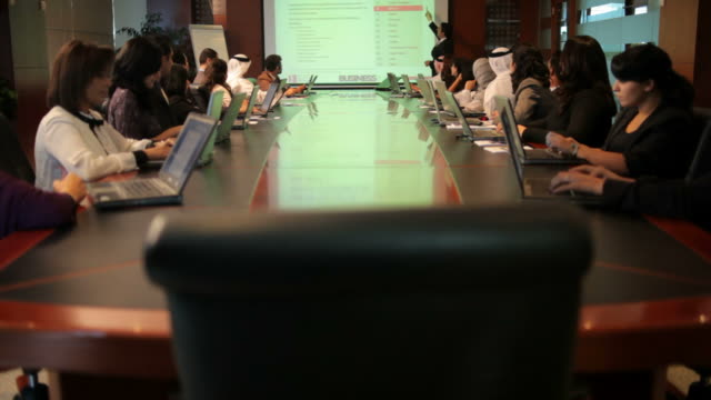 tracking shot showing arab businessmen and women sitting around a conference table working on their laptops. - persian gulf stock videos & royalty-free footage