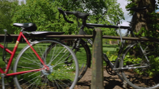 tracking shot showing bicycles lined up against railings in cambridge, uk. - cambridge england stock videos and b-roll footage