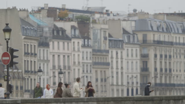 Tracking shot showing people crossing Paris' Petit Pont, France.