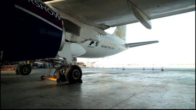 tracking shot showing the underside of a gulf air plane parked in a hangar. the camera tracks around to show the formula one grand prix 2009 logo. - directly below stock videos & royalty-free footage