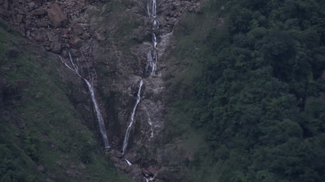 Tracking shot showing water tumbling down the length of an astonishingly tall, winding waterfall in India.