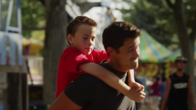 vídeos de stock, filmes e b-roll de tracking shot, slow motion of father piggybacking son at carnival / american fork, utah, united states - sobre os ombros