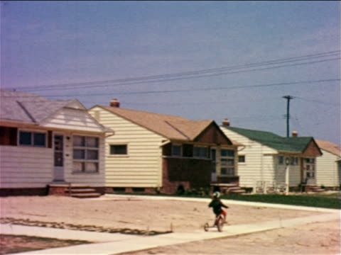 1957 tracking shot small child riding tricycle on sidewalk past small suburban homes / northeast Ohio