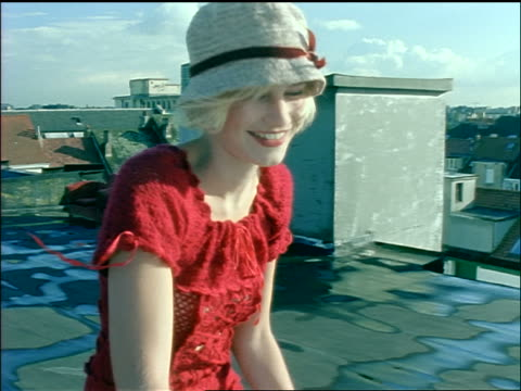tracking shot smiling young blonde woman with hat + dress riding bike on roof of building - sonnenhut stock-videos und b-roll-filmmaterial