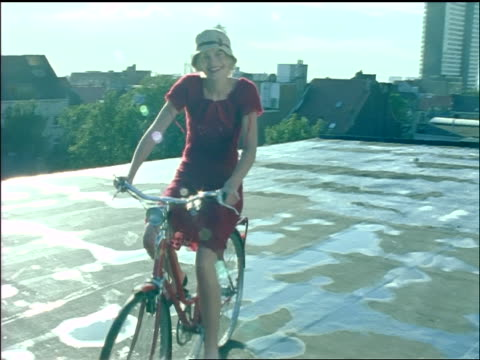 tracking shot smiling young blonde woman with hat + dress riding bike on roof of building past camera - sonnenhut stock-videos und b-roll-filmmaterial