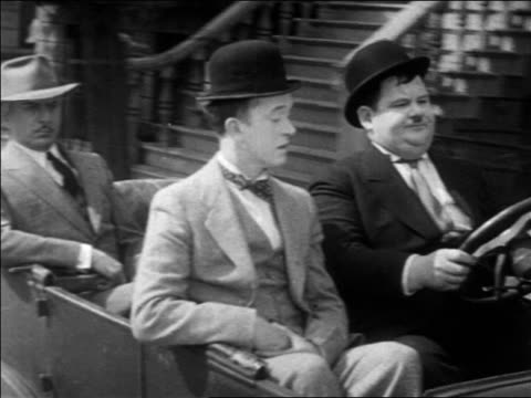vidéos et rushes de b/w 1931 tracking shot stan laurel oliver hardy driving in convertible car with man in backseat / feature - 1931