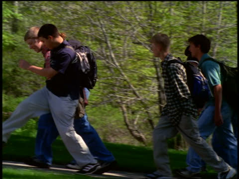 SIDE VIEW tracking shot students with backpacks walking on sidewalk with trees in background