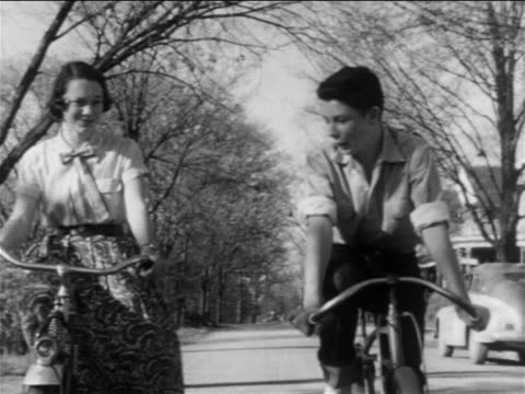 vídeos y material grabado en eventos de stock de b/w 1955 tracking shot teenage boy + girl riding bicycles on tree-lined suburban street + talking / educational - bicicleta antigua