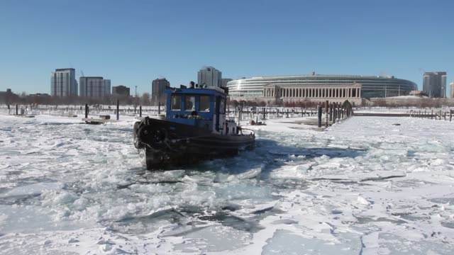 tracking shot the tugboat commissioner breaks up ice in burnham harbor near soldier field on january 21 2014 in chicago illinois a weather system... - コミッショナー点の映像素材/bロール